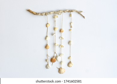 Handmade seashell mobile. Seashells hanging in the middle of a white background. Sea and summer decoration.