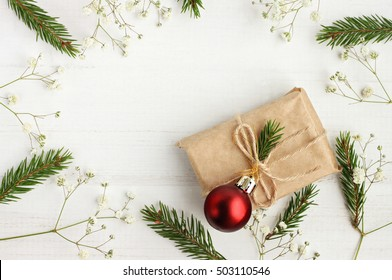 Handmade simple Christmas gift empty top view background. Craft present box, new year tree twigs, wooden table.
