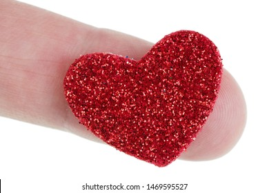 A handmade small red paper heart is strewn with sparkles and lies on a finger