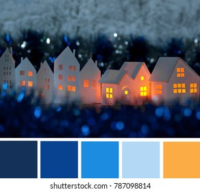 Handmade small white cardboard houses with cut windows on dark blue bokeh foreground and background. Winter decoration. Color palette swatches, natural combination of colors, inspired by winter mood.