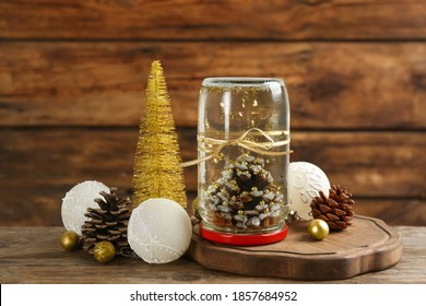Handmade snow globe and Christmas decorations on wooden table