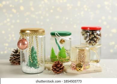 Handmade snow globes and fir cones on light table