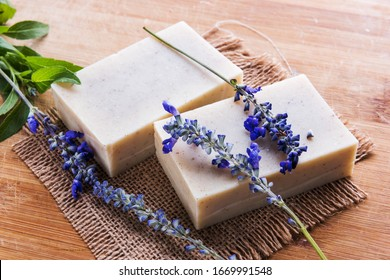 Handmade soap bars with lavender flowers on wooden table