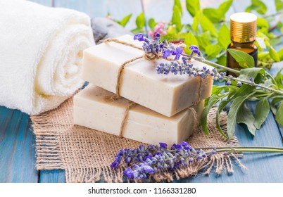 Handmade soap, fresh plants and essential oils as well as handmade soap on a blue table