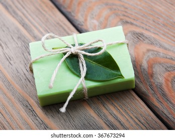 Handmade soap with green leaves on a old wooden background
