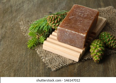 Hand-made soap and green pine cones on wooden background