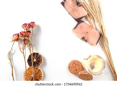 A handmade soaps brown-pink color with an orange tint and dried slices of oranges, roses flowers, pastel vanila candle and spikes of wheat on a white background with wooden texture .The concept of
