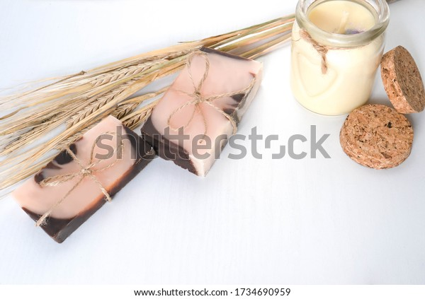 A handmade soaps brown-pink color with an orange tint , pastel vanila candle and spikes of wheat on a white background with wooden texture .The concept of accessories for personal care and spa