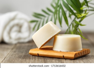 Handmade solid shampoo soap bar on wooden dish. Green leaves above and towel on the background. Zero waste, eco friendly product