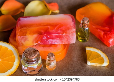 handmade spa fruit soap and bottles with cosmetic oil and orange closeup