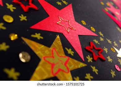 Handmade Stars in Gold And Red On A Black Surface
