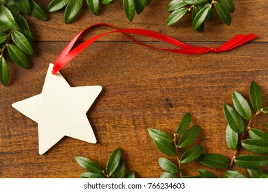 Handmade, star-shaped blank Christmas gift tag with red ribbon o