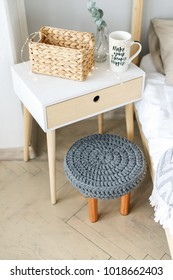 handmade stool with a knitted seat and wooden legs in a modern interior