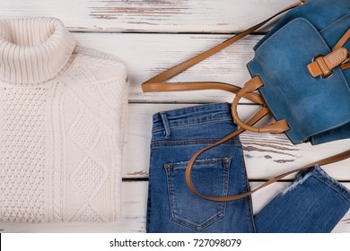 Handmade sweater, jeans and backpack. Casual warm outfit idea. Fall-winter women's clothing concept for fashion blog.