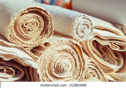 Handmade textile in retro style - natural  fabric of flax and cotton. Canvas and burlap in rolls closeup - homespun fabric of handwork.