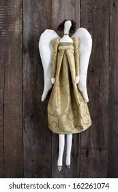 Handmade Tilda angel doll over wooden background