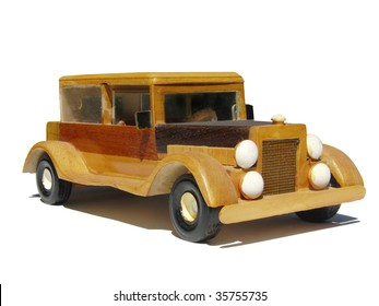 A handmade toy car, crafted of wood. Photographed on a white background.
