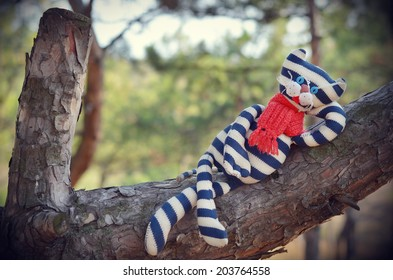 Handmade toy cat wearing red scarf is laying on a pine stem