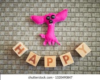 Handmade toy dog and wooden alphabet blocks spelling happy on grey carpet. Educational toys for children in preschool and kindergarten.