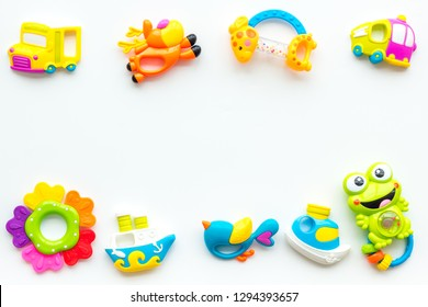 Handmade toys for newborn babies, plastic and wooden rattle on white background top view space for text frame