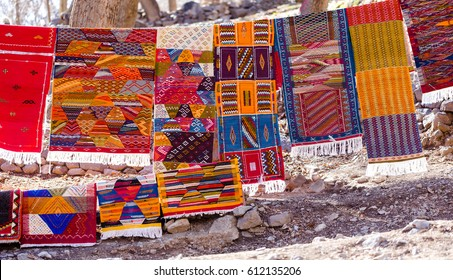 Handmade traditional in vibrant colors berber rugs hanged on line in berber village in Atlas mountains, Morocco