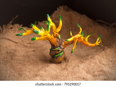 Handmade tree from polymer clay isolated on sackcloth texture. Tree of life painting with acrylic paint
