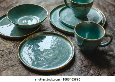Handmade turquoise earthenware on a brown background.