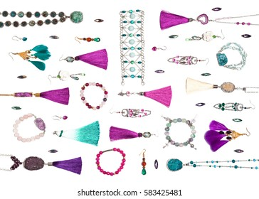 Handmade turquoise and violet bijouterie with gems, tassels and feathers, lying flat on the white background, top view