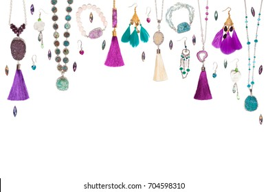 Handmade turquoise and violet bijouterie with gems, tassels and feathers, top view, lying flat on the white horizontal background