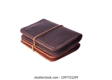 Handmade two red and brown leather cardholders with rubber band isolated on white background closeup. Stock photo of handmade luxury accessories.