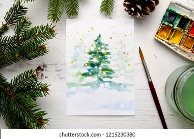 Handmade watercolor Christmas card on the work table with watercolor box, brushes, palette and fir branches and pine cones. Top view