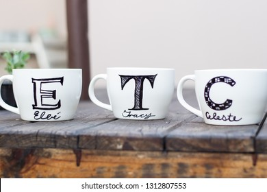 Handmade white ceramic mugs with permanent marker drawing on wooden table diy cup gift