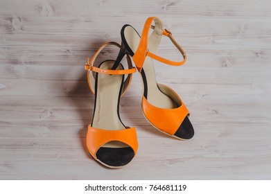 hand-made women's dance shoes made of genuine leather on the wooden surface macro photography. orange color colored style