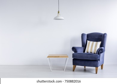 Handmade wood and metal modern table standing next to royal blue armchair with striped cushion