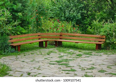 Handmade Wooden Bench In The Public Garden. Pavement Of Natural Stone Tiles In The Foreground.