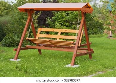 Handmade wooden bench swing in garden