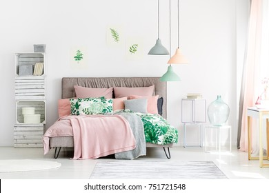 Handmade wooden cabinet next to bed with pink blanket in bright bedroom with floral motif