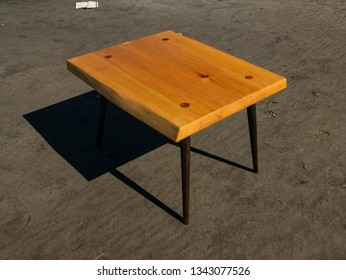 handmade wooden coffee table stands on the sand. craftwork