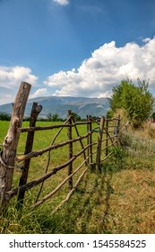 A handmade wooden fence made of thin rods. The old fence of tree trunks, rural landscape, nature wallpaper background.