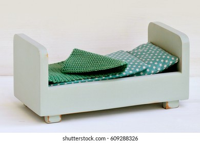 Handmade wooden miniature bed for dollhouse.