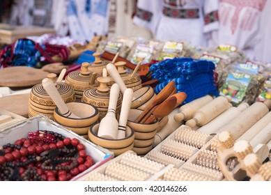 Handmade wooden, vintage kitchen utensils for sale at the market. Various wooden kitchen tools. Different wooden tableware. Wooden stand under the hot pan.