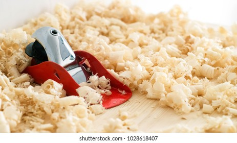 Handmade woodwork: a small red plane on the boards in shavings