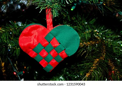 Handmade Woven Red and Green Heart Ornament Hanging on the Christmas Tree