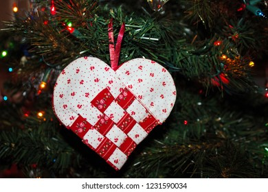 Handmade Woven Red and White Heart Christmas Ornament Hanging on a Christmas Tree