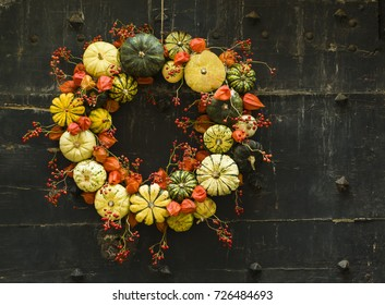 Handmade wreath of small pumpkins and zucchini on a vintage door