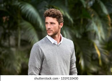 Handomse guy with stubble in grey, looking away