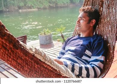 Handosme indian man relaxing on hammock at riverside kanchanaburi thailand hoiliday
