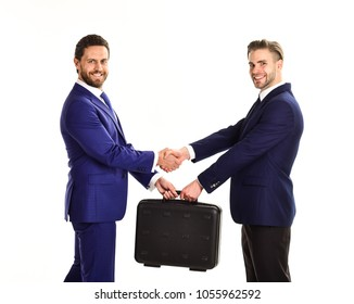 Handover of suitcase in hands of partners on white background. Businessmen with happy faces shaking hands and hold briefcase. Business exchange between businessmen in suits. Successful deal concept.