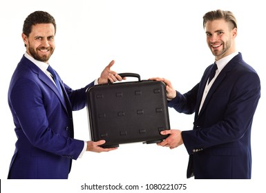 Handover of suitcase in hands of partners on white background. Businessmen with happy faces hold black briefcase. Business exchange between businessmen in classic suits. Business and deal concept.