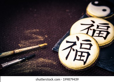 "Hand-painted cookies with chinese characters ""fortune"" and harmony sign yin yang. Selective focus."